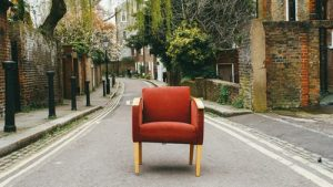 Old red chair in the street before upholsterers Edinburgh re-upholster it