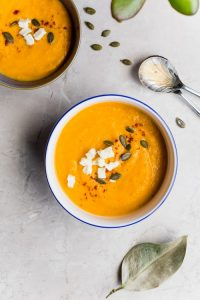 Bowl of healthy butternut squash soup topped with feta cheese, seeds and herbs