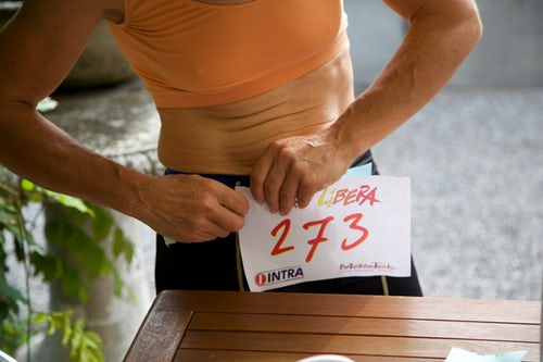 Runner pinning race number onto leggings while getting fit